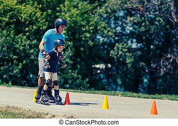 Senior man, teacher of roller skating with little boy