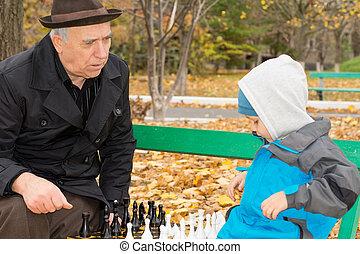 Senior man teaching his grandson chess - Senior man teaching...