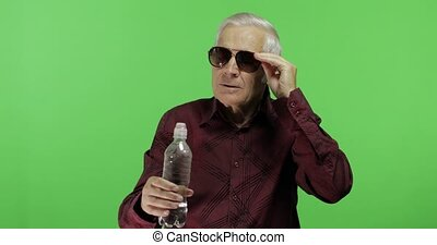Senior man tourist in sunglasses tired of high temperatures...