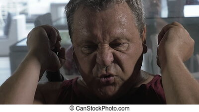 Senior man training hard in the gym, he has a heavy breathing and sweat all over the body