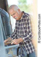 senior man turning wheel to adjust industrial machinery