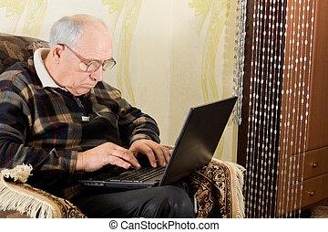Senior man typing on his laptop computer