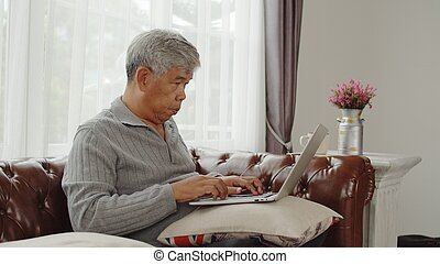 Senior man typing on laptop computer with happy