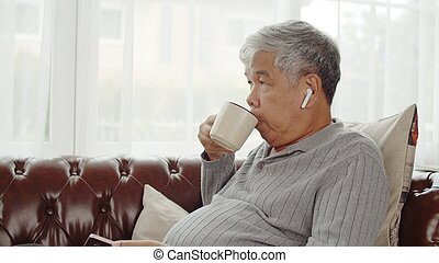 Senior man use wireless earphone listening music and drink coffee