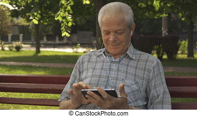 Senior man uses tablet on the bench