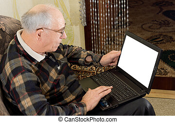 Senior man using a laptop computer - High angle view showing...
