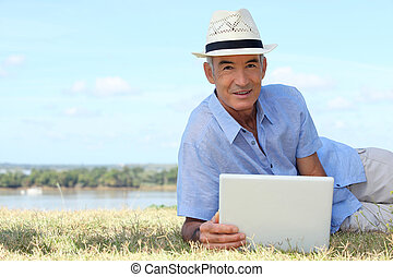 Senior man using a laptop computer on a riverbank