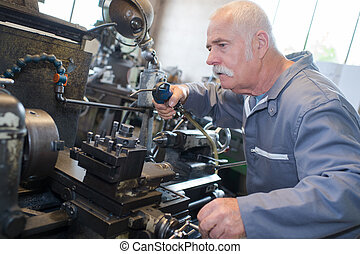 Senior man using air line on machinery