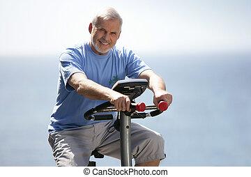 Senior man using an exercise bike outdoors