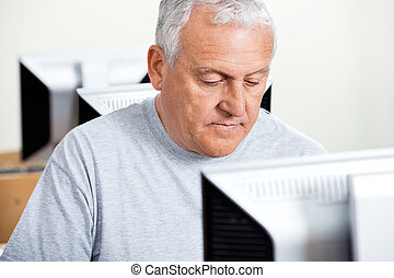 Senior Man Using Computer In Classroom