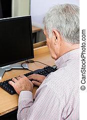 Senior Man Using Desktop PC In Class