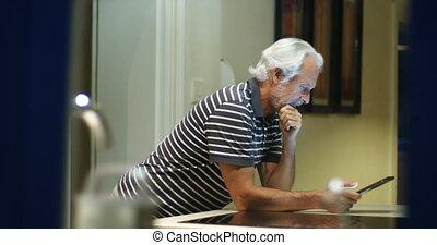 Senior man using digital tablet at home 4k - Active senior...