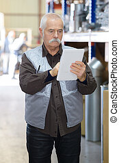 senior man using digital tablet in warehouse