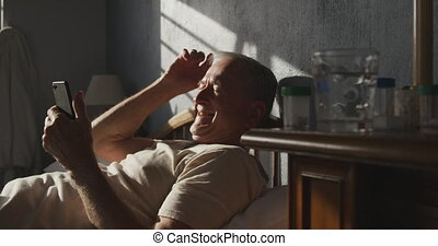 Senior man using digital tablet on bed
