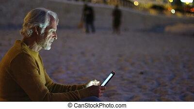 Senior man using digital tablet on the beach 4k - Active...