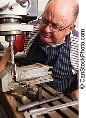 senior man using industrial drilling machine