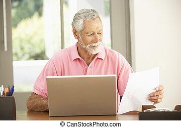 Senior Man Using Laptop At Home