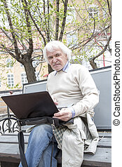 Senior man using laptop computer outdoors
