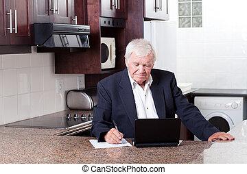 senior man using laptop in home kitchen