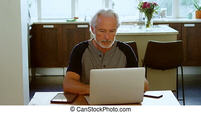 Senior man using laptop on table 4k