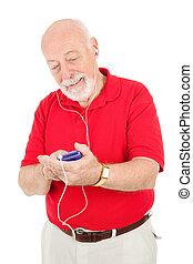 Senior Man Using MP3 Player - Senior man browsing his music ...