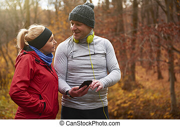 Senior man using phone during jogging