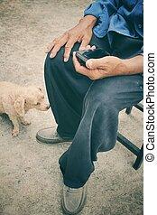 Senior man using smart phone with dog