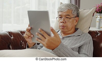 Senior man using tablet in relaxing time at home