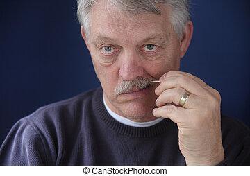 senior man using toothpick
