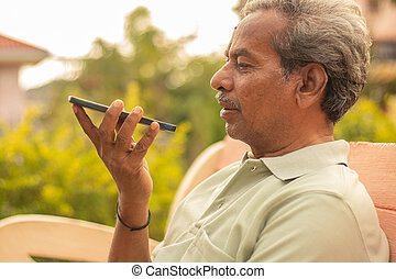 Senior man using virtual assistant in phone - Indian elder man using voice command on mobile - old man talking on smartphone at outdoor.