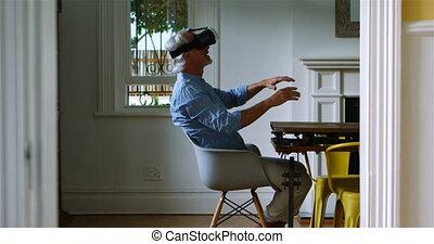 Senior man using virtual reality headset at home 4k