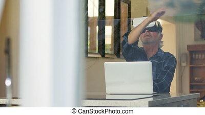 Senior man using virtual reality headset in kitchen 4k