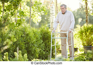 Senior Man Using Walker in Park