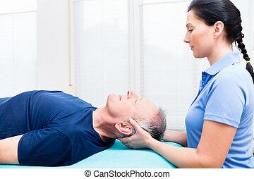 Senior man visiting physiotherapist for massage