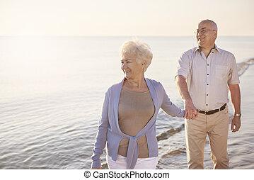 Senior man walking behind his wife