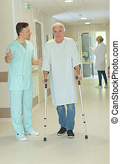 senior man walking on crutches in hospital corridor