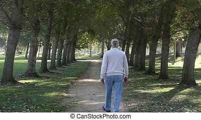 senior man walking on park path
