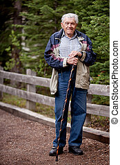 Senior Man Walking - A senior man walking outdoors on a path