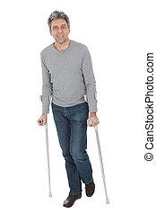 Senior man walking using crutches