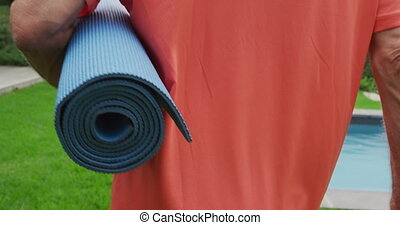 Senior man walking with a yoga mat - Rear view close up of a...