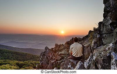 Senior man watches sunrise over blue ridge