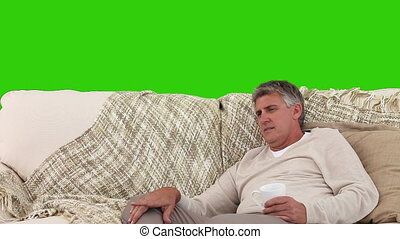 Senior man watching tv while he is drinking a cup of tea
