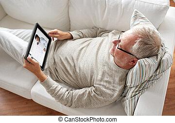 senior man watching webinar on tablet at home