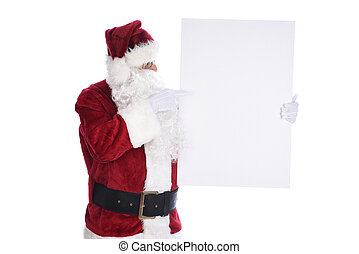 Senior man wearing a traditional Santa Claus costume holding a white sign Pointing at the blank space ready for copy.  Isolated on white.