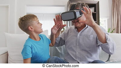 Senior man wearing a Virtual Reality headset with her ...