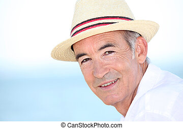 Senior man wearing at hat by the coast