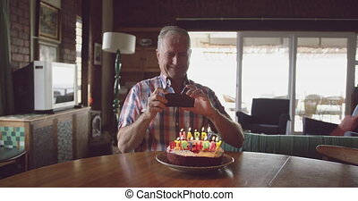 Senior man with a birthday cake at home - Front view of a ...