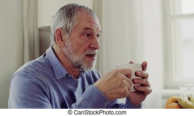 Senior man with a cup of coffee sitting at the table at home, talking to somebody.