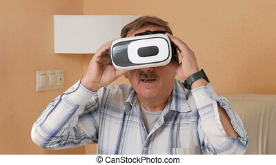 Senior man with a mustache is sitting with a helmet virtual reality on the couch at home. He wonders what they see and try to touch your hands to virtual items