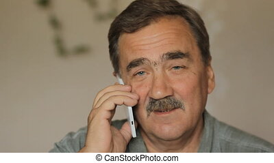 Senior man with a mustache talking on a cell phone. Business...